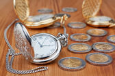 Group pocket watch against the background of euro coins. — Stock Photo