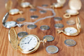 Group gold pocket watch against the euro coins. — Stock Photo