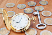 Gold pocket watch on the background euro coins and keys. — Stock Photo