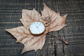 Pocket watch the autumn leaves. On a wooden texture. — Stock Photo
