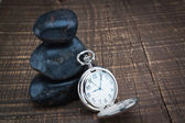 Pocket watch near the stones for spa. On a wooden texture. — Stock Photo