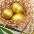 Gold eggs in the nest. Concept for Easter. - Stock Photo