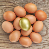Group of eggs and one golden. At Easter. On a wooden texture. — Stock Photo