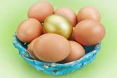 Cestino di Pasqua con uova d'oro e blue. su uno sfondo verde. — Foto Stock