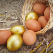 Royalty-Free Stock Photo: Group gold eggs spilled out of a basket. At Easter.