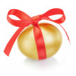 Golden easter egg with red bow. On a white background. — Zdjęcie stockowe