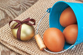 Blue bucket and easter golden eggs scattered on sackcloth. — Stock Photo