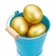 Blue bucket filled with golden Easter eggs. On a white backgroun — Stock Photo