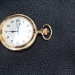 Antique gold pocket watch on a textured black leather. Close-up. — Stock Photo