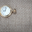 Antique pocket watch on a textured burlap. Close-up. — Stock Photo