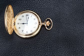 Antique gold pocket watch on a textured black leather. Close-up. — Stockfoto