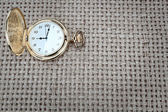 Antique pocket watch on a textured burlap. Close-up. — 图库照片