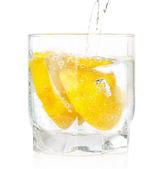 A glass of cold drink with a lemon from the fridge. On a white b — Stock Photo