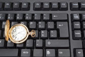 Gold pocket watch against the background of a computer keyboard. — Stock Photo