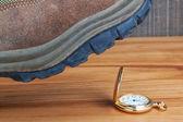 Metafora-ammazzare il tempo. stivali sull'orologio d'oro. — Foto Stock