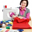 Woman worker sews on the sewing machine. — Stock Photo
