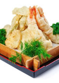 Fried calamari with parsley and dill in a decorative wooden plat — Stock Photo