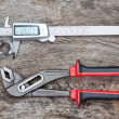 Foto Stock: Caliper and adjustable wrench with detail on wooden texture.