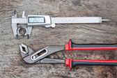 Caliper and adjustable wrench with a detail on a wooden texture. — Stock Photo