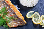 Gorgeous delicious piece of fish on a background of greens and r — Stock Photo