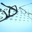 Table Golovin and glasses eye tests on blue background. — Stok Fotoğraf #24022777