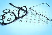 Table Golovin and glasses eye tests on a blue background. — Stock Photo