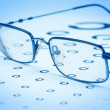 Stockfoto: Glasses to improve vision on test card. In blue tones.