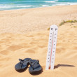 Slippers on the beach beside the thermometer and the sea. Summer — Stock Photo