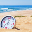 Stock Photo: Classic analog clocks in sand on beach near sea. For