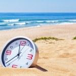 klassieke analoge klokken in het zand op het strand in de buurt van de zee. voor — Stockfoto