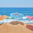 Small beach umbrellas on a beach on a background of the sea. — Stock Photo