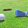 Zdjęcie stockowe: Golf stick ball near hole. Against background of grass.