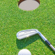 Golf putter ball near hole in vertical format. Against t — Stockfoto #24692651