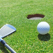 Golf stick and ball on grass near hole. — Foto Stock #24692657
