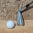 Golf ball and stick inverted wooden support in sand. Close-u — Foto Stock #24692747