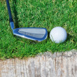 Stockfoto: Golf ball and stick inverted wooden support on grass.