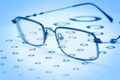 Glasses to improve vision on the test card. In blue tones. — Stockfoto