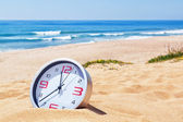 Classic analog clocks in the sand on the beach near the sea. For — Stock Photo