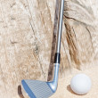 Stock Photo: Golf stick and ball on sand. Close-up.