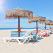 Stock Photo: Wooden beach umbrellas and sunbeds on a beach on a sunny day. Fo