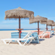 Wooden beach umbrellas and sunbeds on the beach. For the holiday — Stock Photo