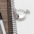 Pocket watch and pen on the notebook into a cell. In the office. — Stock Photo #25235233