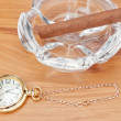 Stock Photo: Retro image of gold pocket watch and a Havana cigar in the ashtr