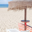 Wooden beach umbrella and sun bed on the beach on a sunny day. F — Stock Photo