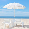 Beautiful white beach umbrella and sun bed on a sunny beach. For — Stock Photo
