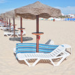 Wooden beach umbrellas in a row on a sunny beach. For the rest. — Stock Photo #25235337