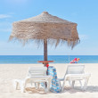Wooden beach umbrella and sun bed on the beach, in the backgroun — Stock Photo