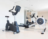 Exercise bike and rowing simulator in the luxury gym close-up. — Stock Photo