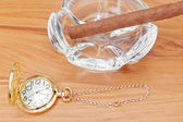 Retro image of gold pocket watch and a Havana cigar in the ashtr — Stock Photo