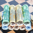 Royalty-Free Stock Photo: Paper money and coins as the euro on the chessboard. Concept Ima